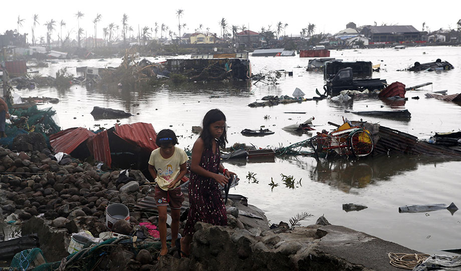 Residents walk near vehicles and debris floating on a river after Super Typhoon Haiyan devastated Tacloban city in central Philippines